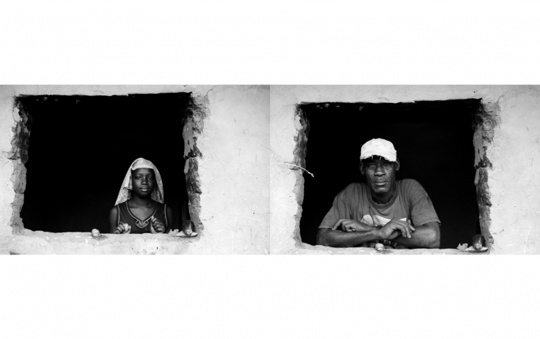 Retratos de una joven y un señor de raza negra asomados a la ventana de su casa.
